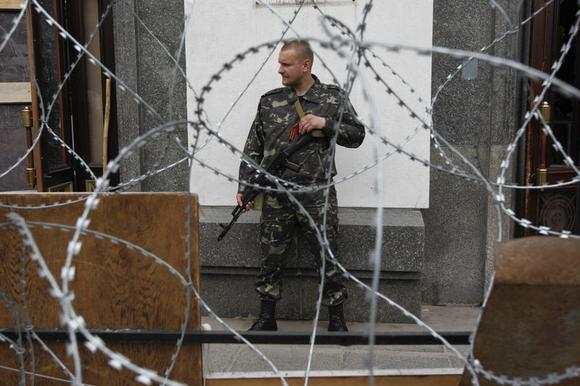 An armed pro-Russian activist stands guard outside an administrative building in the eastern Ukrainian city of Luhansk May 12, 2014. REUTERS/Valentyn Ogirenko