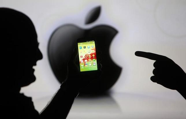 Men are silhouetted against a video screen with an Apple Inc logo as they pose with a Samsung Galaxy S3 smartphone in this photo illustration taken in the central Bosnian town of Zenica, May 17, 2013.  REUTERS/Dado Ruvic
