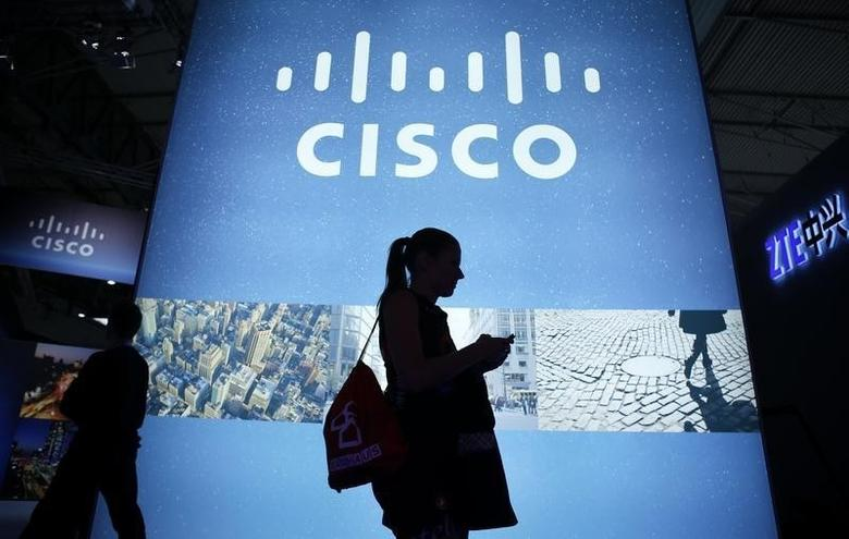 A visitor walks past a Cisco advertising panel as she looks at her mobile phone at the Mobile World Congress in Barcelona February 27, 2014. REUTERS/Albert Gea/Files