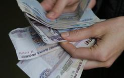 Продавец пересчитывает рублевые купюры на рынке в Москве 3 марта 2014 года. Рубль начал торги четверга на бирже умеренным снижением к бивалютной корзине и ее компонентам, отыграв все факторы роста предыдущих дней - геополитическую стабильность и поддержку налогового периода. REUTERS/Maxim Shemetov