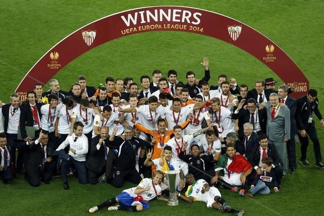 Sevilla players and officials celebrate with the trophy after defeating Benfica in their Europa League final soccer match at the Juventus stadium in Turin May 14, 2014. REUTERS/Alessandro Garofalo