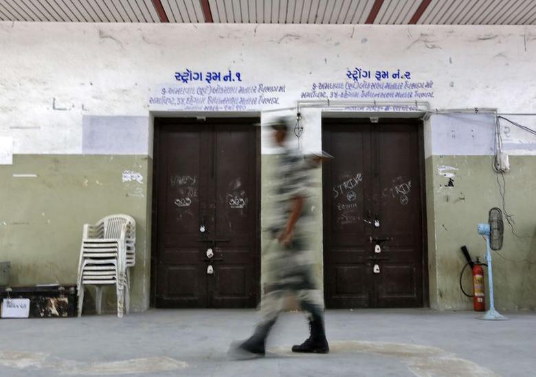 A security personnel stands guard outside a sealed strong room where electronic voting machines (EVM) are kept, in Ahmedabad May 15, 2014. REUTERS/Amit Dave