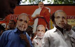 Сторонники Нарендры Моди в масках с его изображением стоят у офиса партии BJP в Бомбее 16 мая 2014 года. Кандидат от оппозиции Нарендра Моди станет новым премьер-министром Индии, а его соратники получат большинство в парламенте, показывают предварительные результаты выборов. REUTERS/Danish Siddiqui