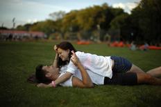 Пара лежит на траве в Парке Горького в Москве 14 августа 2013 года. Наступающие выходные в Москве будут теплыми, но могут принести небольшие осадки, ожидают синоптики. REUTERS/Lucy Nicholson