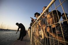 An ultra-Orthodox Jewish boy looks on as men pray during the Tashlich ritual near the shore of the Mediterranean Sea in the southern city of Ashdod September 12, 2013, ahead of Yom Kippur, the Jewish Day of Atonement, which starts at sundown Friday. Tashlich is a ritual of casting away sins of the past year into the water. REUTERS/Amir Cohen