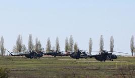 Российские военные вертолёты на поле у посёлка Северный в Белгородской области 25 апреля 2014 года. Украина обратила внимание на спад активности российских военных вблизи своих границ, на фоне объявления Кремля о сворачивании маневров в приграничном районе, хотя НАТО не нашло подтверждений отводу войск. REUTERS/Sergei Khakhalev