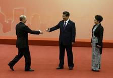 El presidente ruso Vladimir Putin (a la izquierda) es recibido por el presidente chino Xi Jinping y por su esposa Peng Liyuan,  Shanghái, mayo 20, 2014.