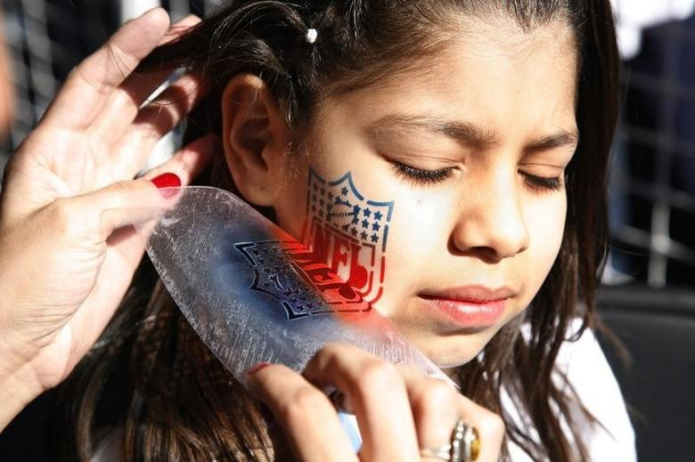 A child has the National Football League logo airbrushed on her cheek at the NFL Experience in Glendale, Arizona, January 30, 2008.       REUTERS/Rick Wilking