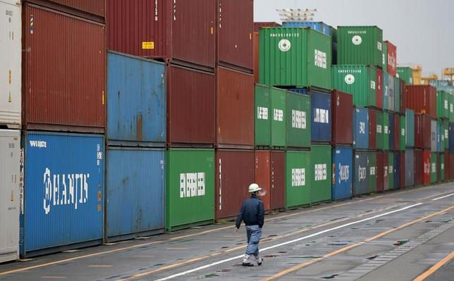 A worker walks in a container area at a port in Tokyo April 21, 2014. REUTERS/Toru Hanai