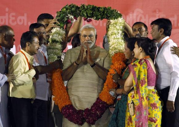 Narendra Modi, who will be the next prime minister , wears a garland presented to him by his supporters at a public meeting in Ahmedabad May 20, 2014. REUTERS/Amit Dave