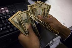 Un cajero cuenta dinero en una tienda de la minorista Macy's durante el día de Acción de Gracias en Nueva York, nov 28 2013. La inflación de Estados Unidos se está acelerando desde sus actuales tasas bajas y llegará al 2 por ciento para fines de este año, de acuerdo con un sondeo de Reuters entre economistas. REUTERS/Eric Thayer