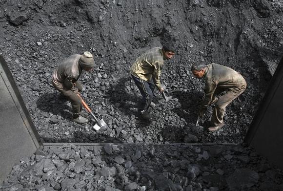 Labourers load coal on trucks at Bari Brahamina on the outskirts of Jammu March 16, 2012. REUTERS/Mukesh Gupta/Files
