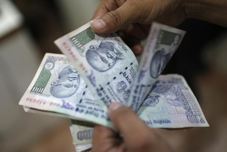 An employee counts rupees inside a private money exchange office in New Delhi July 5, 2013. REUTERS/Adnan Abidi/Files