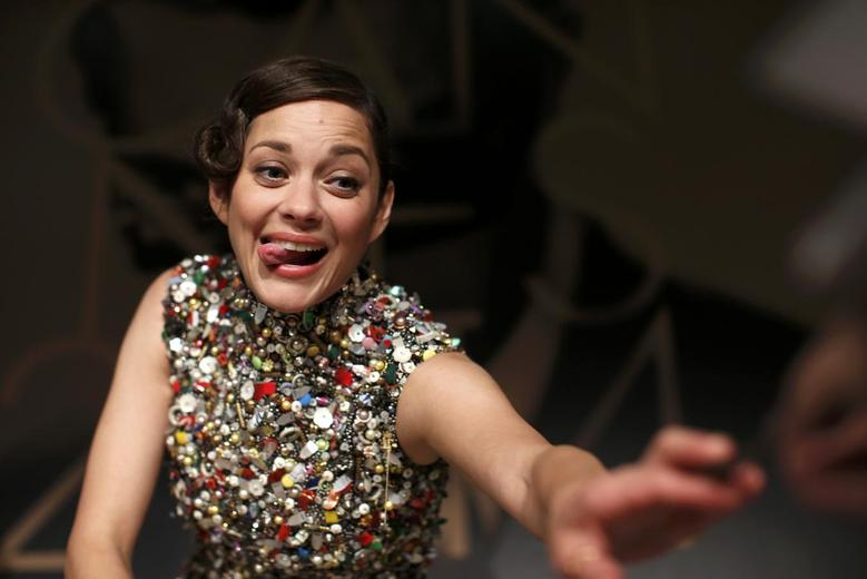 Cast member Marion Cotillard reacts as she signs autographs at the end of a news conference for the film ''Deux jours, une nuit'' (Two Days, One Night) in competition at the 67th Cannes Film Festival in Cannes May 20, 2014.          REUTERS/Benoit Tessier