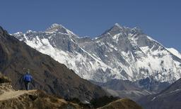 A tourist looks at a view of Mt. Everest from the hills of Syangboche in Nepal December 3, 2009. REUTERS/Gopal Chitrakar