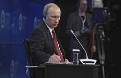 Президент России Владимир Путин на деловомо форуме в Санкт-Петербурге 23 мая 2014 года. Владимир Путин пообещал дешевое долгосрочное финансирование для ускорения темпов роста экономики, близкой к стагнации. REUTERS/Mikhail Klimentyev/RIA Novosti/Kremlin