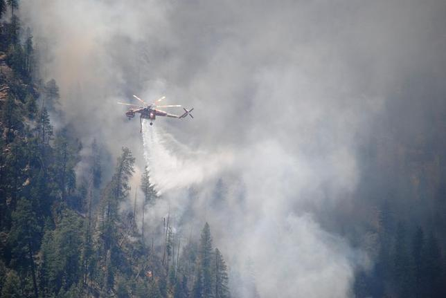 A water-dropping helicopter makes its delivery at the Slide Fire in Oak Tree Canyon near Sedona, Arizona in this May 22, 2014 handout photo released to Reuters May 23, 2014.   REUTERS/U.S. Forest Service/Handout via Reuters