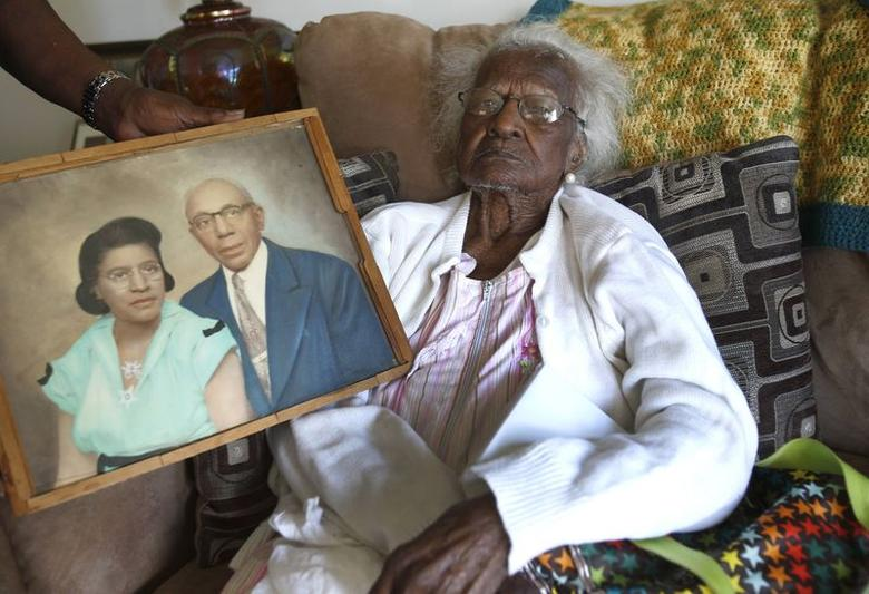 Jeralean Talley sits on her couch, as a photograph showing her and her late husband Alfred is held next to her, on her 115th birthday in her home in Inkster, Michigan May 23, 2014.  REUTERS/Rebecca Cook
