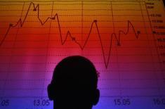 Силуэт мужчины, стоящего у экрана с динамикой индекса FTSE MIB, Рим, 9 августа 2011 года. Европейские фондовые рынки растут за счет Италии, где на выборах в Европейский парламент большинство получила левоцентристская Демократическая партия, возглавляемая премьер-министром Маттео Ренци. REUTERS/Tony Gentile