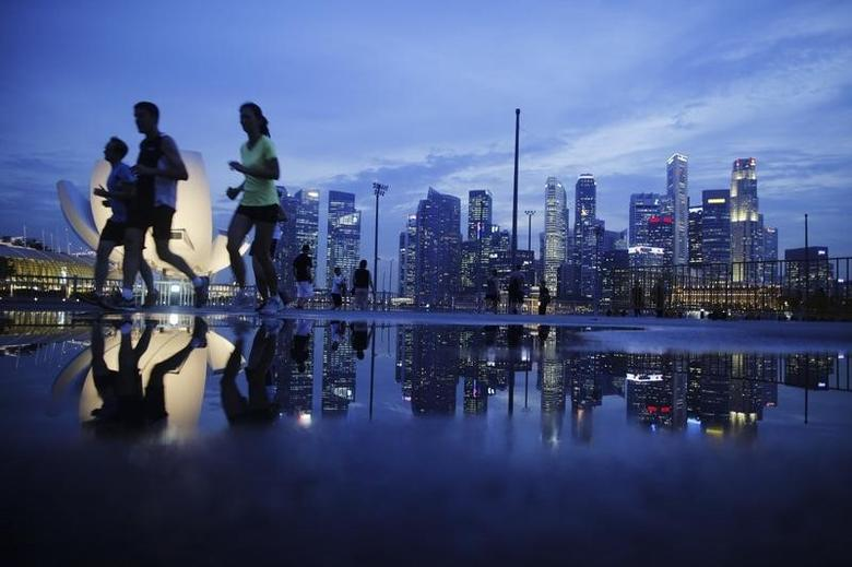 Joggers run past as the skyline of Singapore's financial district is seen in the background April 21, 2014. REUTERS/Edgar Su