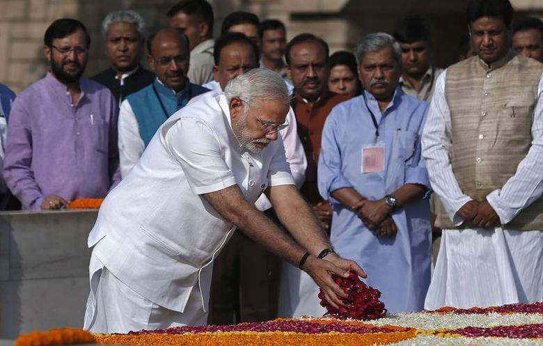 Prime Minister-designate Narendra Modi scatters rose petals at the Mahatma Gandhi memorial at Rajghat ahead of his swearing-in ceremony, in New Delhi May 26, 2014. REUTERS/Adnan Abidi
