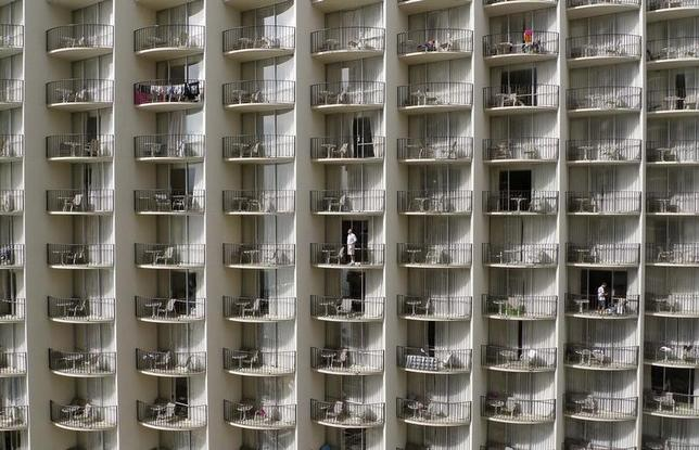 Men stand at the balconies of their hotel rooms on Waikiki Beach in Honolulu, Hawaii, December 30, 2009.    REUTERS/Larry Downing