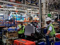 Un grupo de empleados al interior de la planta de General Motors en Talegaon, India, sep 4, 2012. General Motors India dijo que comenzaría a exportar vehículos desde el país y que comenzaría a vender una versión conducida por la izquierda de su Chevrolet Beat a Chile en el primer trimestre de 2015. REUTERS/Danish Siddiqui