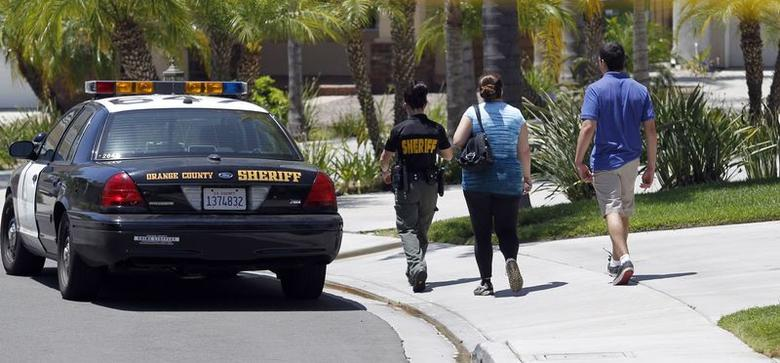 An Orange County Sheriff deputy escorts a couple to their home on a street near a house where four people were found dead, in Mission Viejo, California May 27, 2014.  REUTERS/Alex Gallardo