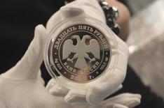 Коллекционная монета номиналом 25 рублей на презентации в Москве 25 апреля 2012 года. Рубль дешевеет в первые минуты сессии среды на фоне снижения активности экспортеров к конце месяца и при сохраняющейся геополитической напряженности. REUTERS/Yana Soboleva