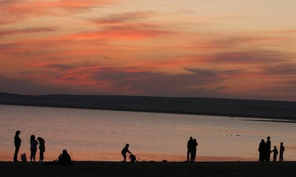 People walk beside a lake during the second day of Eid al-Adha celebrations in Fayoum, around 100 km southwest of Cairo, November 28, 2009. REUTERS/Asmaa Waguih