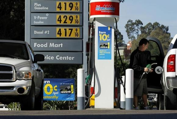 A man stands near gas prices at a petrol kiosk in Dal Mar, California March 1, 2011.   REUTERS/Mike Blake
