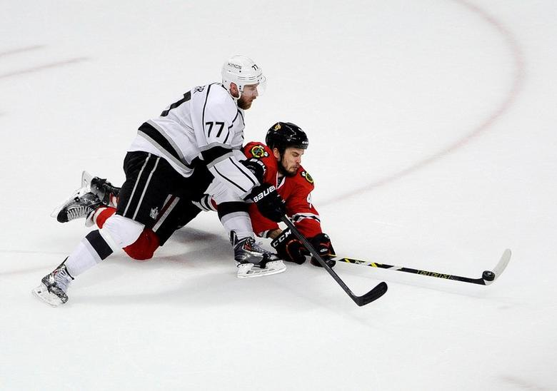 May 28, 2014; Chicago, IL, USA; iLos Angeles Kings center Jeff Carter (77) and Chicago Blackhawks defenseman Niklas Hjalmarsson (4) go for the puck during the third period in game five of the Western Conference Final of the 2014 Stanley Cup Playoffs at  the United Center. The Chicago Blackhawks defeated the Los Angeles Kings 5-4 in the second overtime. Mandatory Credit: David Banks-USA TODAY Sports
