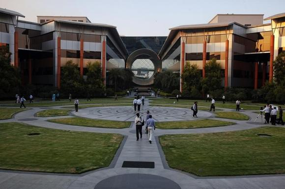 Employees walk in front of a building dubbed the ''washing machine'', a well-known landmark built by Infosys at the Electronics City IT district in Bangalore, February 28, 2012. REUTERS/Vivek Prakash/Files