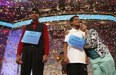Sriram Hathwar of Painted Post, New York, gets a hug from his mother Roopa (R) as he and Ansun Sujoe (L) of Fort Worth, Texas are joint winners of the 87th annual Scripps National Spelling Bee at National Harbor, Maryland May 29, 2014.   REUTERS/Kevin Lamarque