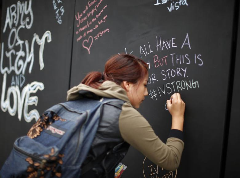 A student signs on a remembrance wall in the Isla Vista neighborhood of Santa Barbara, California May 27, 2014.  REUTERS/Lucy Nicholson