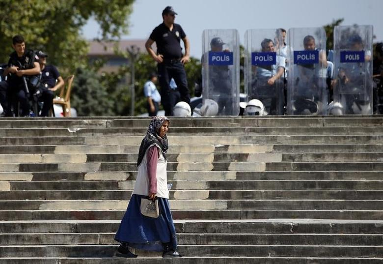 A woman walks as Turkish police guard the entrance of Gezi Park at Taksim Square in Istanbul June 17, 2013.  REUTERS/Marko Djurica