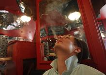 Rusia se arriesga a encender la ira de sus 44 millones de fumadores el domingo cuando extienda la prohibición de fumar a restaurantes y bares como una medida más en la batalla para acabar con el hábito de uno de los países con mayor consumo de tabaco del mundo. En la imagen, un hombre fuma en un café de Moscú, el  31 de mayo de 2013. REUTERS/Maxim Shemetov