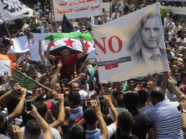 Lebanese protesters join Syrian refugees opposing Syria's President Bashar al-Assad as they hold flags and chant slogans during a demonstration against the participation of the Syrian refugees in the Syrian election in Lebanon, after their Friday prayers in Tripoli, northern Lebanon May 30, 2014.  REUTERS/Omar Ibrahim