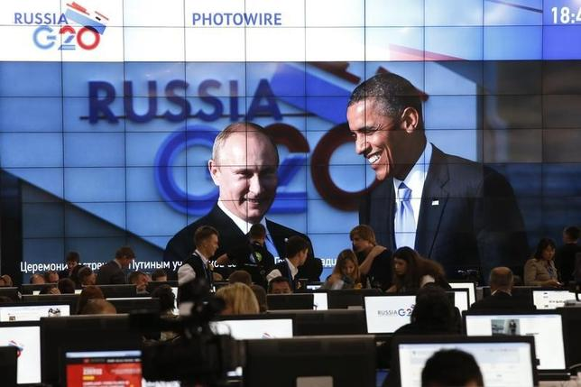 Russian President Vladimir Putin (L) and U.S. President Barack Obama are pictured on a video screen installed in the press centre of the G20 Summit in Strelna near St. Petersburg, September 5, 2013.           REUTERS/Grigory Dukor