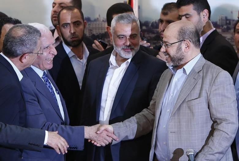 Senior Fatah official Azzam Al-Ahmed (L) shakes hands with senior Hamas leader Moussa Abu Marzouq after announcing a reconciliation agreement in Gaza City April 23, 2014. REUTERS/Suhaib Salem