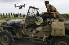 A history enthusiast sits in a jeep as he watches a Boeing Bell V-22 Osprey as it takes off in Colleville-sur-Mer, on the Normandy coast June 2, 2014. REUTERS/Regis Duvignau