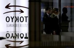 Люди проходят мимо логотипа Токийской фондовой биржи в её здании в Токио 30 января 2014 года. Азиатские фондовые рынки, кроме Китая, выросли во вторник благодаря хорошей макроэкономической статистике США и Китая. REUTERS/Toru Hanai