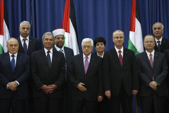 Palestinian Prime Minister Rami Hamdallah (4th L) and Palestinian President Mahmoud Abbas (3rd L) pose for a group photo with Palestinian ministers during a swearing-in ceremony of the unity government, in the West Bank city of Ramallah June 2, 2014.  REUTERS/Mohamad Torokman