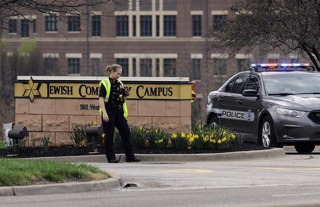 An Overland Park Kansas police officer guards the entrance to the scene of a shooting at the Jewish Community Center of Greater Kansas City in Overland Park, Kansas April 13, 2014.  REUTERS/Dave Kaup