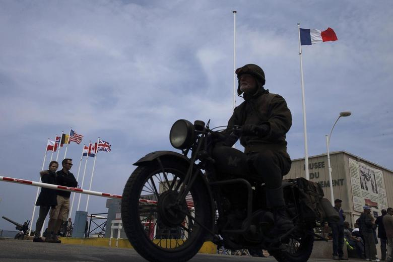 An history enthusiast, wearing a U.S. World War  Two uniform rides a vintage motorbike in the streets in Arromanches, on the Normandy coast June 1, 2014.   REUTERS/Pascal Rossignol