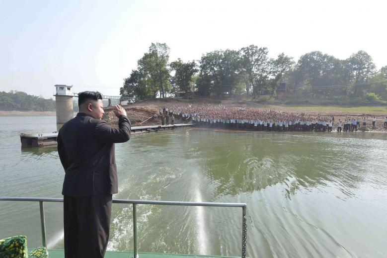 North Korean leader Kim Jong Un (L) acknowledges the crowd during a visit to a construction site of a resort for scientists in this undated photo released by North Korea's Korean Central News Agency (KCNA) in Pyongyang May 29, 2014. REUTERS/KCNA