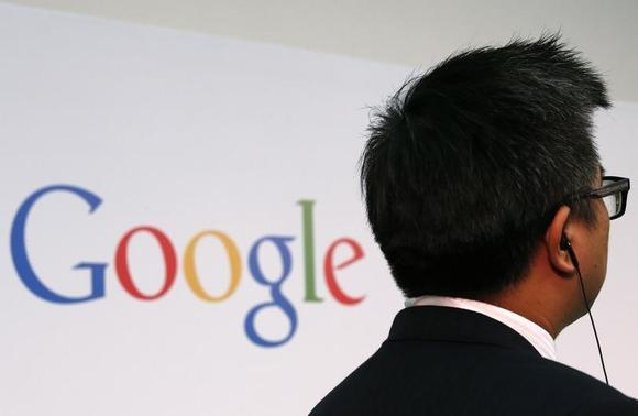 A man stands in front of a Google logo before a talk titled 'Connecting with the World Empowering Young Entrepreneurs for the New Digital Age' by Google Executive Chairman Eric Schmidt (not seen) at the Chinese University of Hong Kong November 4, 2013. REUTERS/Bobby Yip/Files