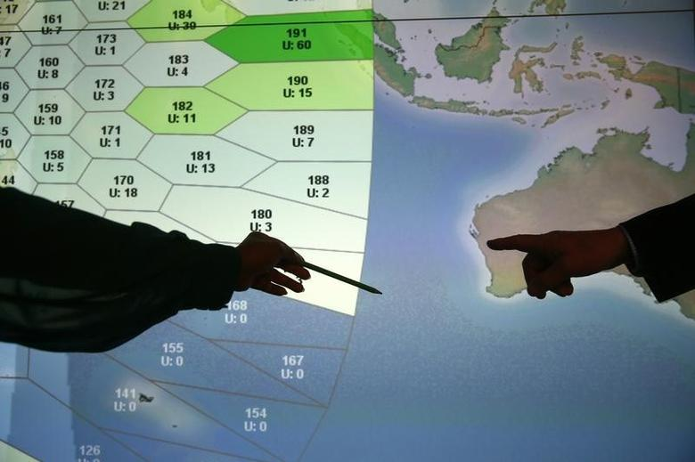 Member of staff at satellite communications company Inmarsat point to a section of the screen showing the southern Indian Ocean to the west of Australia, at their headquarters in London March 25, 2014. Britain's Inmarsat used a wave phenomenon discovered in the nineteenth century to analyse the seven pings its satellite picked up from Malaysia Airlines Flight MH370 to determine its final destination. REUTERS/Andrew Winning
