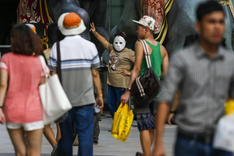 A masked demonstrator gestures during a brief protest against military rule at a shopping mall in Bangkok June 1, 2014. REUTERS/Athit Perawongmetha