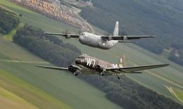 A former U.S. Air Force C-47 Skytrain aircraft (bottom) flies alongside a C-130J Super Hercules aircraft assigned to the 37th Airlift Squadron over Germany in this handout photo taken May 30 and released June 3, 2014. REUTERS/U.S. Air Force/Staff Sgt. Sara Keller/Handout via Reuters